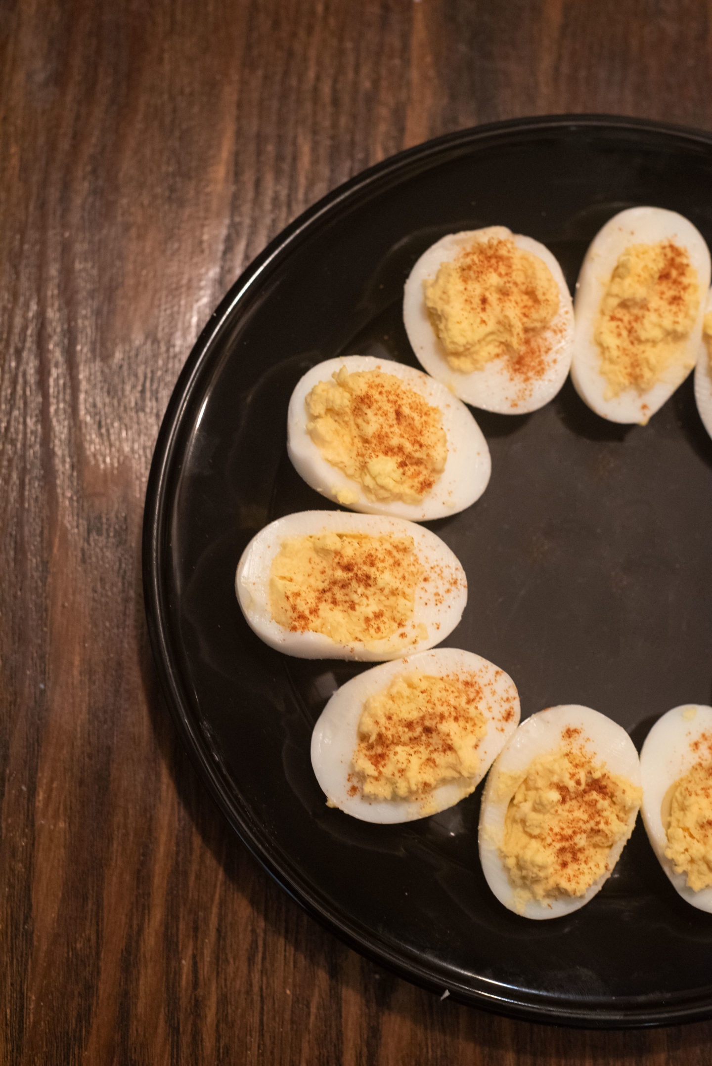 Spicy Deviled Eggs on a black plate