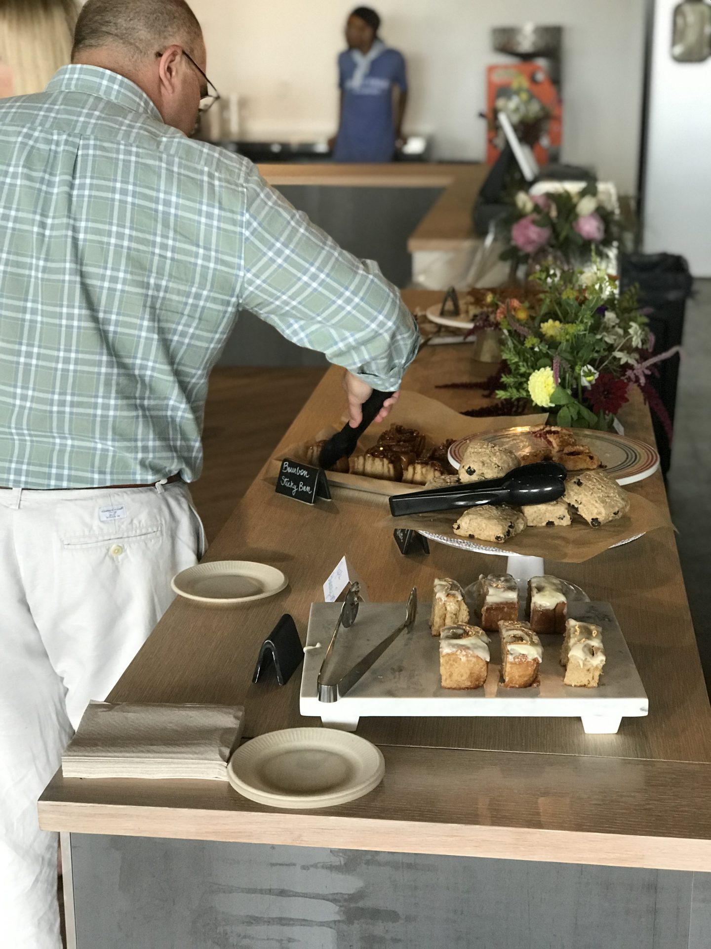Man picking out a dessert from a dessert table