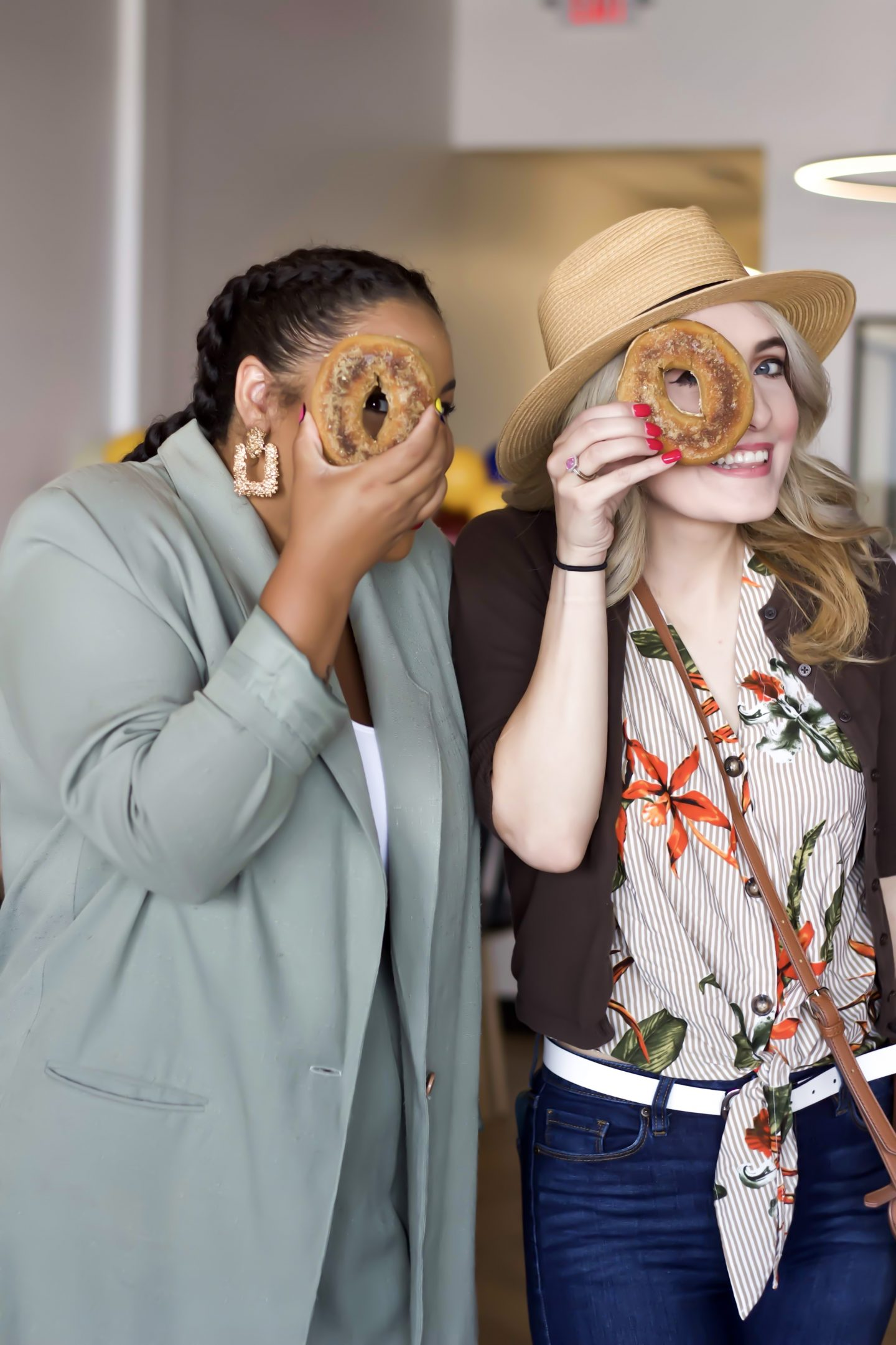 Two girls holding a bagel up to their eye