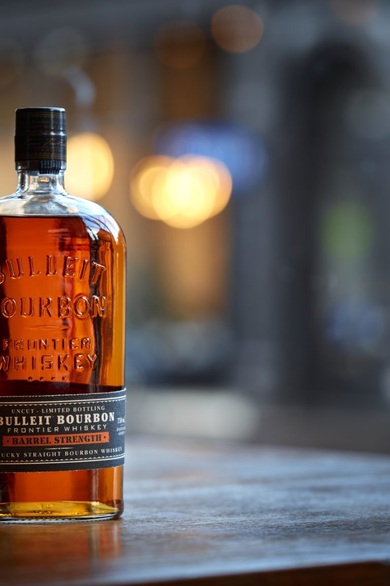 bourbon bottle and bourbon in a rocks glass