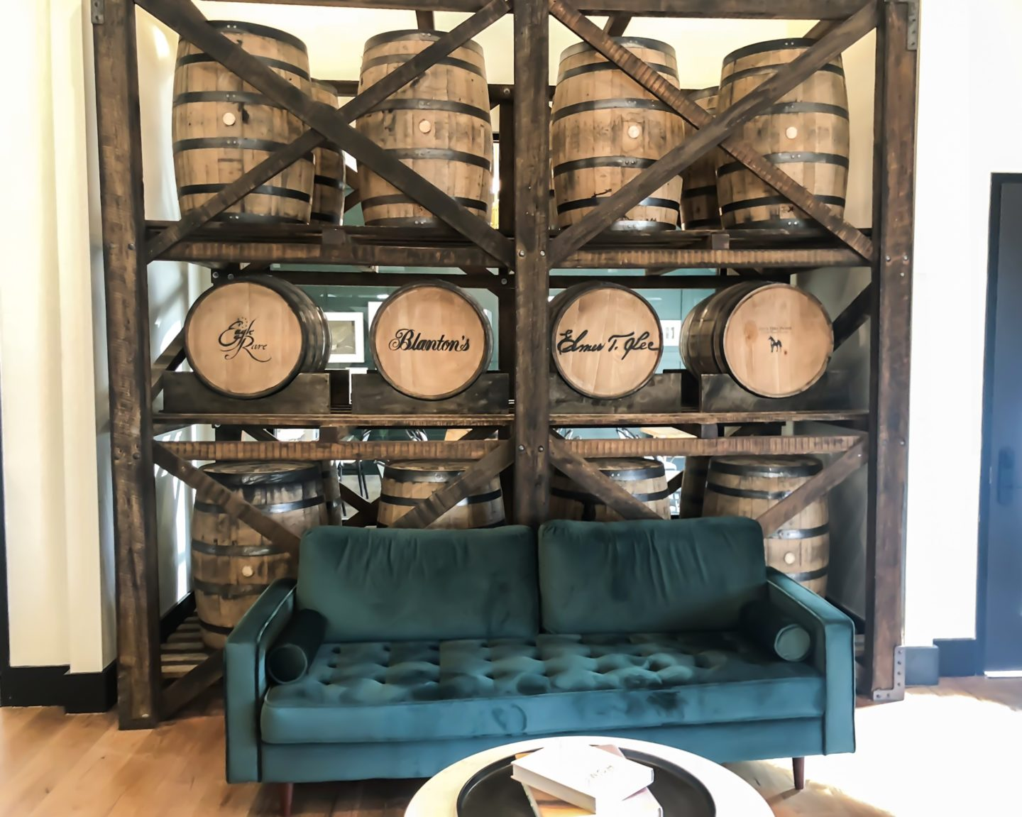 couch in front of a wall of bourbon barrels