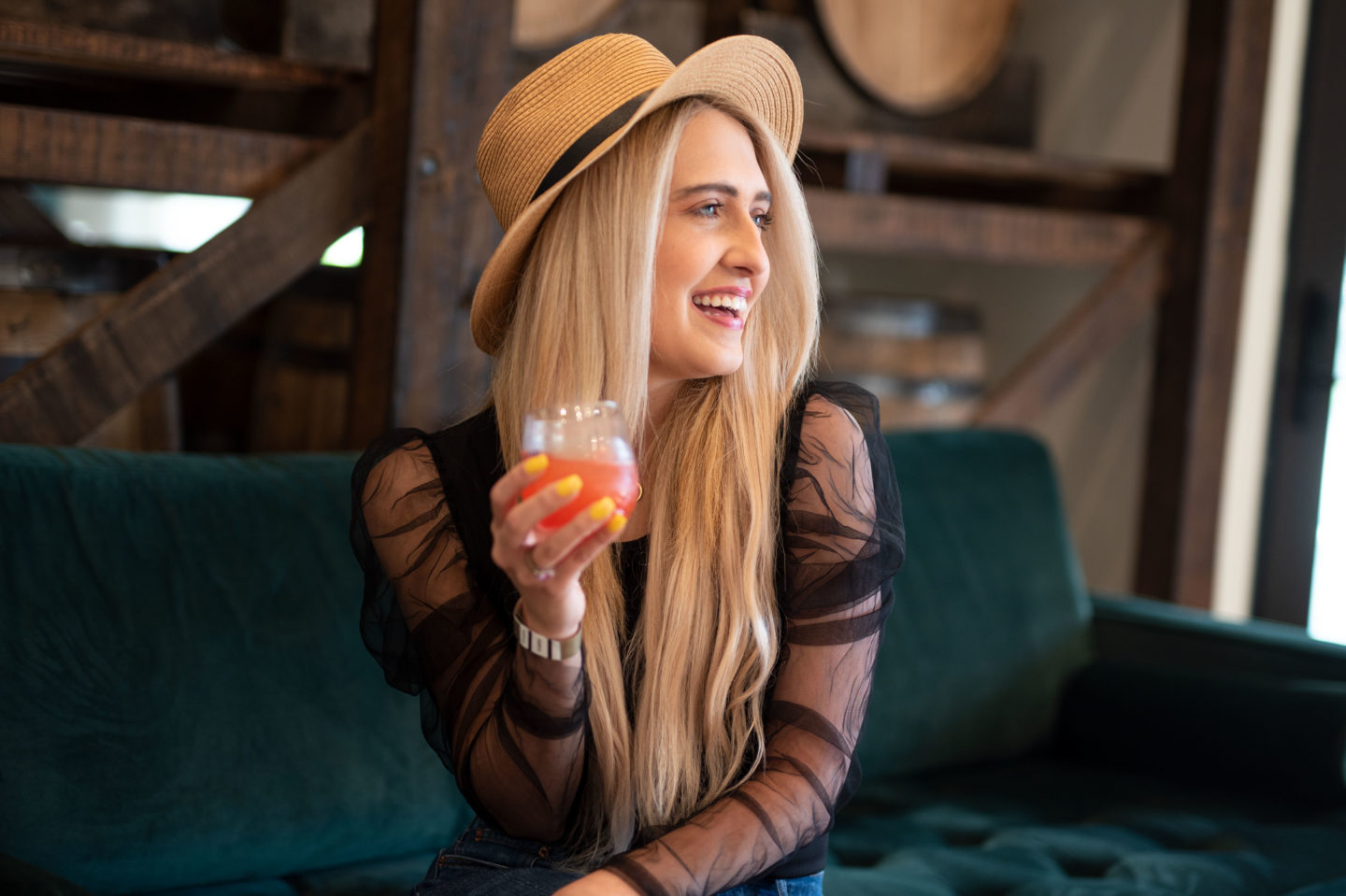 girl in a hat holding a drink smiling