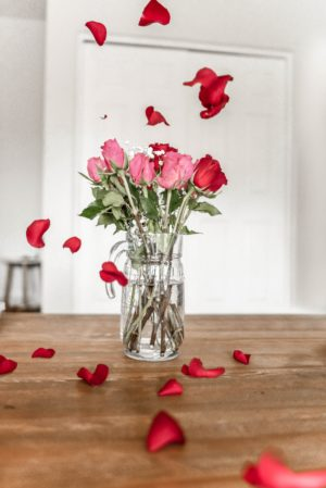 roses in a vase and rose petals