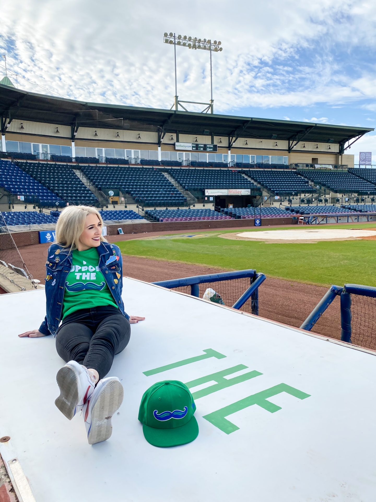 blonde girl sitting on top of the dugout at a ballpark